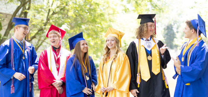 Students in varied colored graduation gowns talk and laugh together candidly.